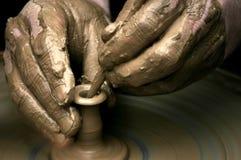 Hände des Töpfers auf Rad des Töpfers Lizenzfreie Stockbilder