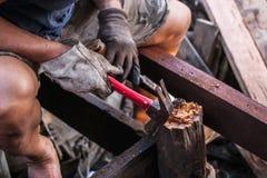 Hände des Tischlers mit Meißel und Hammer in den Händen Lizenzfreie Stockbilder