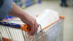 Hände des unbekannten Mädchens auf einer Warenkorbnahaufnahme Im Supermarkt kaufen stock video footage