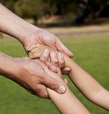 Hände des Vaterholdingjungen und schwingen ihn Lizenzfreies Stockbild