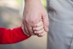 Hände des Vatis und der Tochter Stockbild