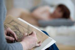 Hände des weiblichen Künstlers zeichnet Skizze vor Aktmodell in der Zeichenklasse lizenzfreie stockfotos