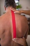 Hände des weiblichen Therapeuten elastisches therapeutisches Band auf hemdloser älterer männlicher Patientenrückseite anbringend Lizenzfreies Stockbild