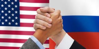 Hände, die über den amerikanischen und russischen Flaggen armwrestling sind Stockfoto