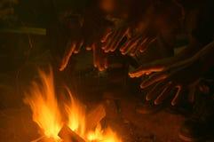 Hände, die über einem hölzernen Feuer sich wärmen Stockfotografie
