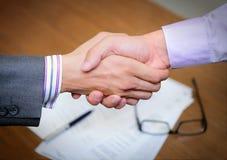 Hände, die über Geschäftsvertrag rütteln Stockbilder