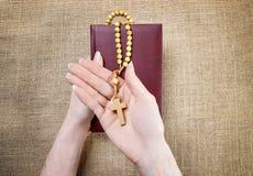 Hände, die alte heilige Bibel und hölzernes Rosenbeet halten Stockfotografie