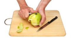 Hände, die Apfel abziehen Stockbild