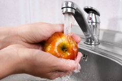 Hände, die Apfel unter Wasser waschen Stockbild