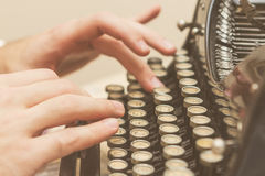 Hände, die auf alte Schreibmaschine schreiben stockfoto