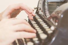 Hände, die auf alte Schreibmaschine schreiben stockbilder