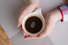 Hände, die auf dem Tisch einen Tasse Kaffee umarmen Lizenzfreies Stockfoto
