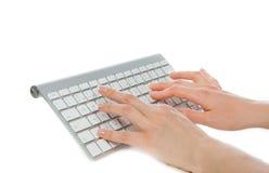Hände, die auf der drahtlosen Computerentfernttastatur schreiben stockfotos