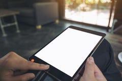 Hände, die auf einen schwarzen Tabletten-PC mit leerem weißem Tischplattenschirm halten, sich berühren und zeigen lizenzfreie stockfotos