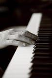 Hände, die auf einer Klaviertastatur stillstehen Stockfoto