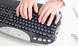 Hände, die auf einer Tastatur schreiben Lizenzfreie Stockfotos