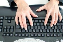 Hände, die auf einer Tastatur schreiben Stockfotos