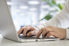 Hände, die auf Laptop-Computer schreiben stockbilder