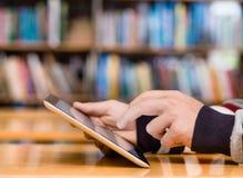 Hände, die auf Tablet-Computer in der Bibliothek schreiben lizenzfreie stockfotografie