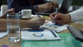 Hände, die auf verschiedene Finanzdiagramme auf Tabelle schreiben stock footage