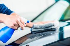 Hände, die Auto mit Sprayreiniger und microfiber Tuch säubern Lizenzfreie Stockfotos