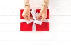 Hände, die Band auf roter Geschenkbox binden lizenzfreie stockfotografie