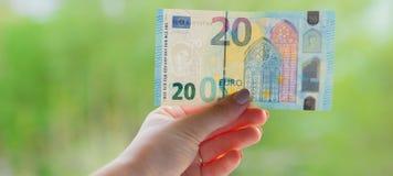 Hände, die Banknote des Euros 20 auf dem grünen Hintergrund halten Überprüfen Sie Euro auf Echtheit Lizenzfreie Stockbilder