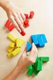 Hände, die Bausteine durch Farbe sortieren stockbilder