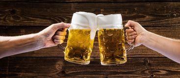 Hände, die Becher bayerisches Bier Oktoberfest halten stockfoto