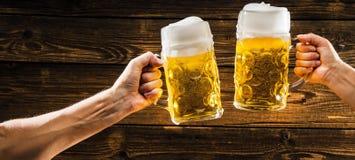 Hände, die Becher bayerisches Bier Oktoberfest halten stockbild