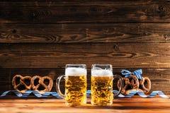 Hände, die Becher bayerisches Bier Oktoberfest halten lizenzfreies stockfoto