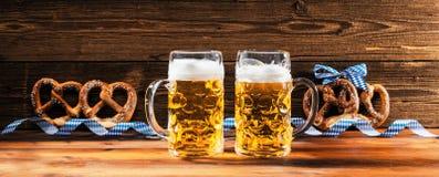 Hände, die Becher bayerisches Bier Oktoberfest halten stockfotografie