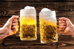 Hände, die Becher bayerisches Bier Oktoberfest halten lizenzfreie stockfotografie