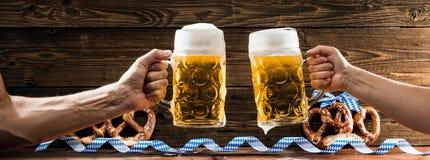 Hände, die Becher bayerisches Bier Oktoberfest halten stockfotos