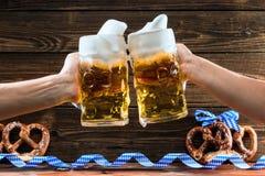 Hände, die Becher bayerisches Bier Oktoberfest halten lizenzfreie stockbilder