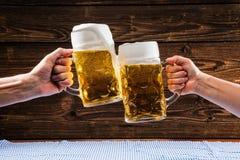 Hände, die Becher bayerisches Bier Oktoberfest halten lizenzfreies stockbild