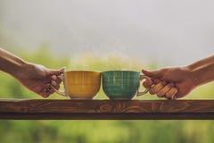 Hände, die Becher mit Heißgetränk, mit Tee auf einem hölzernen Stand halten Stockbild