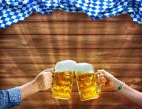 Hände, die Bierkrüge unter bayerischer Flagge halten Lizenzfreie Stockfotografie