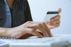 Hände, die blaue Kreditkarte halten und einen Computer für on-line-s verwenden lizenzfreies stockbild