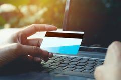 Hände, die blaue Kreditkarte halten und einen Laptop für on-line--sho verwenden Lizenzfreie Stockfotografie