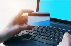 Hände, die blaue Kreditkarte halten und einen Laptop für on-line--sho verwenden Stockfotografie