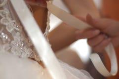 Hände, die Braut in ihr Kleid helfen Stockfotografie