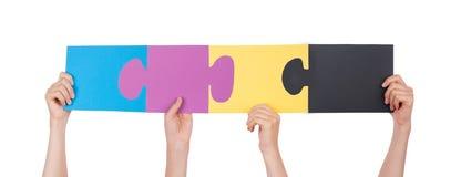 Hände, die bunte Stücke eines Puzzlespiels halten Stockbild