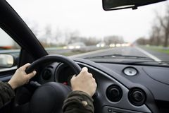 Hände, die das Lenkrad eines Autos auf der Straße halten Stockbild