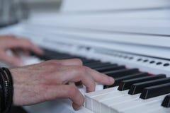 Hände, die das weiße Klavier spielen lizenzfreie stockfotografie