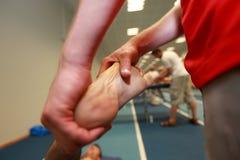 Hände, die den Fuß des erschöpften Athleten nachdem dem Laufen massieren Stockbild