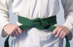 Hände, die den grünen Gürtel auf einem Jugend gekleidet spannen Stockbilder