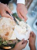 Hände, die den Kuchen schneiden stockbild