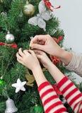 Hände, die den Weihnachtsbaum verzieren Lizenzfreie Stockfotografie