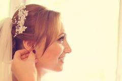 Hände, die der Braut mit Ohrringen helfen Stockfoto